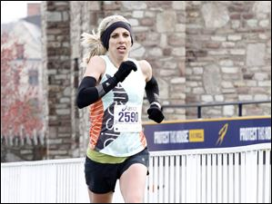 Jennifer Bigham, of Rochester, N.Y., crosses the finish line first for the half marathon female runners.