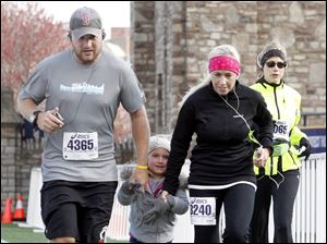 Jared Okoneski, left, and his wife Kelly Okoneski, right, of Perrysburg run across the finish line in the half marathon with their daughter Brooklyn, 4, who joined them for the final 100 yards of the race.