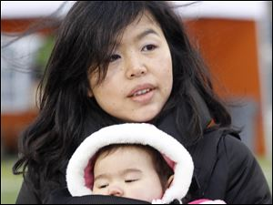 Yumiko Ralston, keeps her daughter Erika Ralston, warm while waiting for her husband to cross the finish line.