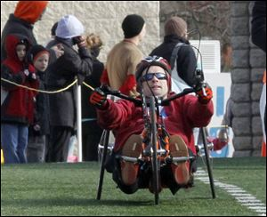 Richard Biggins of Toledo crosses the line first among the wheel-chair competitors in the Glass City Marathon.