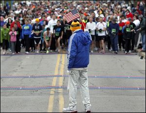 Tom Falvey lofts the flag as runners, at the University of Toledo, await the start of the 5K race. The competitors met winds that gusted to 30 miles an hour.