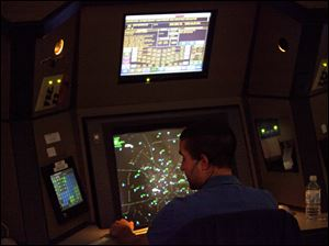 An air traffic controller works in a terminal radar approach control room Monday at the Atlanta TRACON in Peachtree City, Ga.