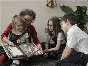 Children's book author Cindy Millen Roberts reads her book 'The Ink Garden of Brother Theophane' to Christ the King school students, from left to right, Clare Dillon, 6, fourth grader Hope Th ayer, Joe Dillon, 10, and Steve Dillon, 8, on Friday.