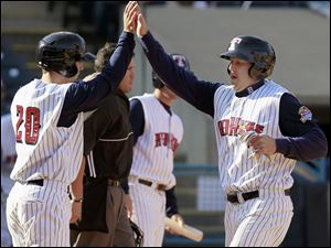 Toledo teammates Scott Sizemore (20) and Scott Thorman (50) high five after they both scored in the third inning of game one.