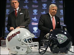 Massachussets chancellor Robert Holub, left, talks with New England Patriots owner Robert Kraft at Gillette Stadium, where the Minutemen will play their home games.