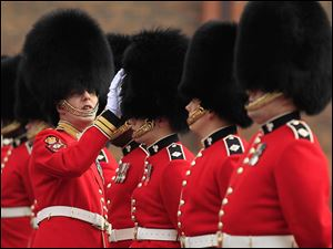 A Company Sergeant Major of the 1st Battalion Irish Guards inspects guardsmen's bearskins, as they take part in an inspection ahead of the royal wedding at their barracks in Windsor, England.