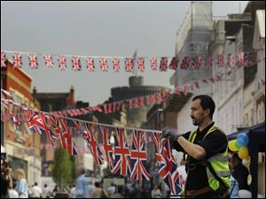 A worker puts up Union flag bunting on a street near Windsor Castle in Windsor, England, ahead of the royal wedding.