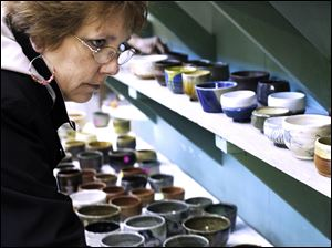 Debbie Lowery of Bradner, Ohio, looks over some of the bowls for sale.