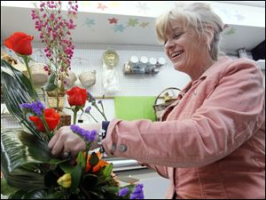 Mary Beth Lorenzen creates a flower arrangement at Schramm's Flowers. Sandy Sack, who owns the West Toledo florist shop, says she expects her store to sell out of Easter lilies this year.