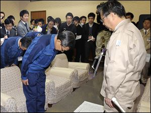 Tokyo Electric Power Co. President Masataka Shimizu, left, bows in apology to Gov. Yuhei Sato, right, of Fukushima prefecture Friday during their meeting at the prefectural office at Fukushima, northeastern Japan.