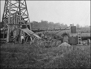 A horse-drawn cart is seen at an oil well at Bradner, Ohio, as a train passes in the background.