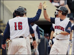 Toledo's Andy Dirks (9), right, is congratulated by Max St-Pierre (16) after hitting his second home run of the game during the fourth inning against Louisville Saturday at Fifth Third Field.