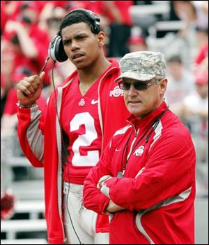 Quarterback Terrelle Pryor and coach Jim Tressel keep a close eye on the game. Pryor didn't play as he continues to recover from an ankle injury.