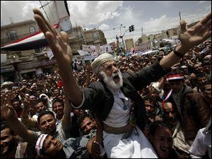 An anti-government protester is carried on others' shoulders in a crowd in the capital demanding the immediate resignation of Yemen's president, Ali Abdullah Saleh.