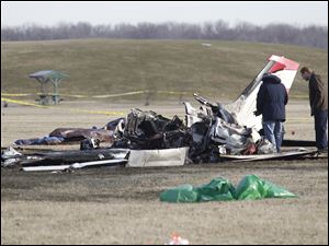 Investigators examine the wreckage of the plane that crashed at Munson Park in Monroe. The crash killed all three men aboard.