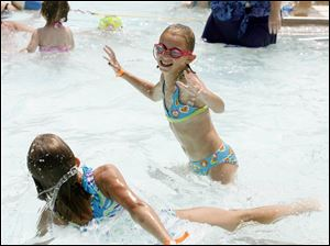 Madison Theis, right, splashes around the water with friend Kelsey Reece, left, while spending the afternoon a