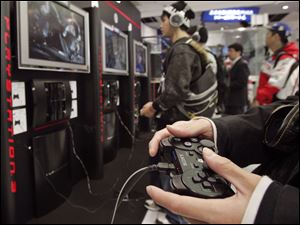 Visitors at the Sony Building in downtown Tokyo play Sony's PlayStation 3 in this file photo.