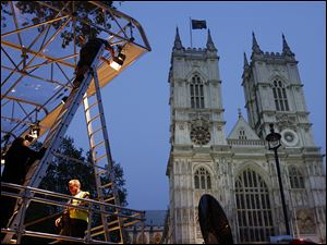 Workers set up lights on a media stand outside Westminster Abbey earlier this week.