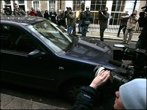 Photo media journalists crowd around the car belonging to Kate Middleton as she leaves her London home in this file photo.