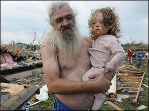Willie Hyde holds 2-year-old granddaughter Sierra Goldsmith near where their house stood in Concord Ala., after a tornado obliterated it Wednesday.