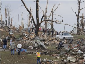 Rescue workers search a hillside Wednesday after what a tornado ripped devastated parts of Concord, Ala.