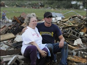 Chase Spradlin, right, comforts Judy Cook after a tornado destroyed her Concord, Ala., home Wednesday.