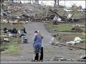 Michael Dunn is hugged by his mother, Patricia Dunn, as they stand in the road that lead to his house, which was completely destroyed after a tornado touched down Wednesday in Concord, Ala.