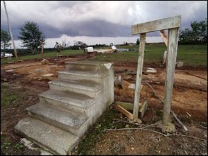 Concrete steps lead to an empty space where a mobile home had sat in Preston, Miss., on Wednesday. The home and one next to it were blown about 100 feet away into a cow pasture. Three related women died at the site.