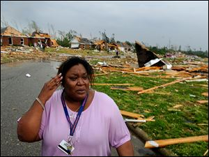 Tamisha Cunningham, who suffered a leg injury when her home was destroyed, looks over the tornado damage near Athens, Ala., on Wednesday while waiting for medical care.