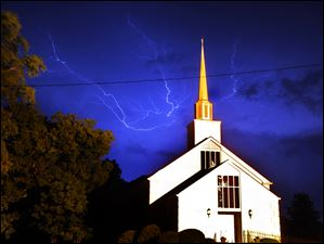 Lightning streaks above Cornith Baptist Church in Athens, Ga., as a line of severe thunderstorms sweep across Georgia in the early morning on Thursday.