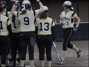 Perrysburg's Lindsay Rich, right, is greeted by her team after hitting a home run against Bowling Green.