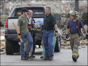 An injured person is removed from the Masters Drive area of Concord, Ala., after a tornado ripped through parts of the town late Wednesday.