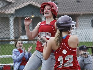 Bowling Green's Hayley Williford, right, and Becca Ruehl celebrate their respective first and second runs off of a hit by teammate Kara Maxey.