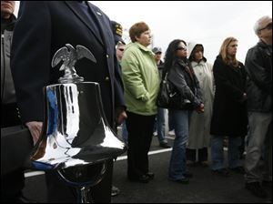 A bell is rung for those killed in the bridge project during a dedication for Tribute Memorial Park.