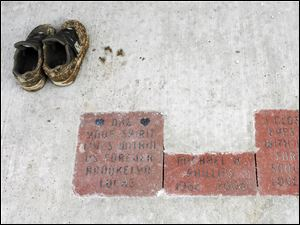 A pair of shoes are left near a bench and bricks dedicated to Michael Phillips at Tribute Memorial Park. Phillips was among five killed during construction.