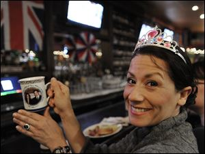 Valerie Malas holds a mug with a photo of Prince William and Kate Middleton to commemorate the couple's royal wedding while she watches the wedding live on television at the Globe Pub in Chicago.