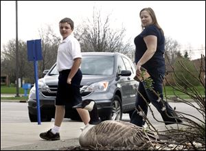 Logan Blockway, 11, left, and his mother, Hanna Blockway, take a gander at a mother goose perching atop her eggs near the entrance to the post office on South Detroit Avenue.