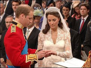 Prince William, left, places the ring on the finger of his bride, Kate Middleton, as they stand at the altar at Westminster Abbey in London.