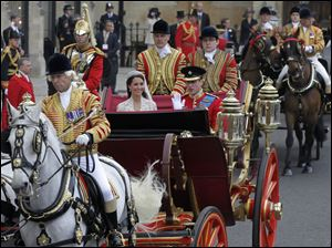 Prince William and Catherine Middleton, now the Duke and Duchess of Cambridge, leave Westminster Abbey in an open horse-drawn carriage after their royal wedding.
