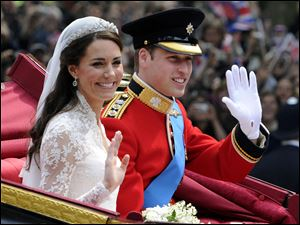 Prince William and Catherine, the Duke and Duchess of Cambridge, wave to onlookers along the route from Westminster Abbey to Buckingham Palace after their royal wedding.