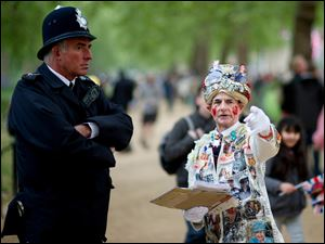 A royal enthusiast  talks to a policeman at the junction of the Mall and  Horse Guards Road prior to the royal wedding in London.