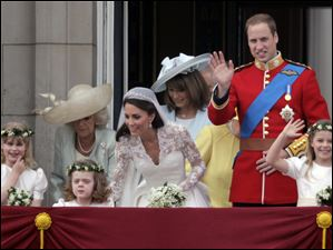 Britain's Prince William and wife Catherine, Duchess of Cambridge, along with Camilla, Duchess of Cornwall, left and Carole Middleton, mother of the bride, encourage the young girls in the wedding party to wave from the balcony of Buckingham Palace.