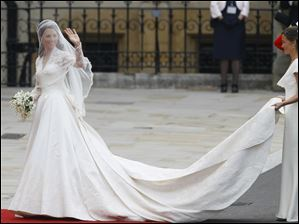Maid of honor Pippa Middleton carries the gown train of sister Kate Middleton as she arrives at Westminster Abbey.
