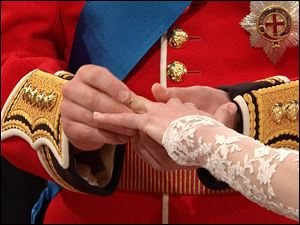 Prince William places a ring on the finger of his bride, Kate Middleton.