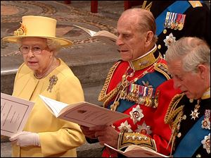 Britain's Queen Elizabeth II, her husband, Prince Philip, center, and her oldest son, Prince Charles, sing during the ceremony at Westminster Abbey.