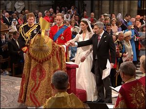 Father of the bride Michael Middleton gives the hand of Kate Middleton to Britain's Prince William.