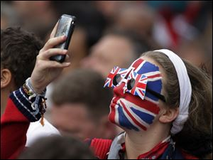 A spectator with her face painted like the Union Jack flag takes a photo outside of Westminster Abbey before the royal wedding.