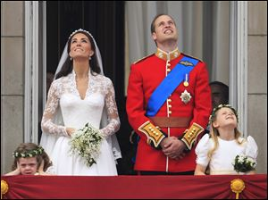 The royal couple watch a flyover of military planes from the balcony of Buckingham Palace after the royal wedding.