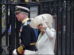 Camilla, Duchess of Cornwall, waves to the crowd outside Westminster Abbey as she arrives with her husband, Prince Charles.