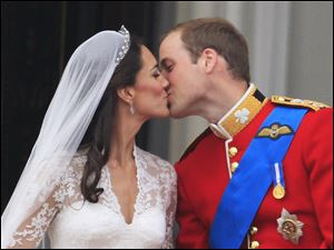 Britain's Prince William kisses his wife Catherine, Duchess of Cambridge, on the balcony of Buckingham Palace.